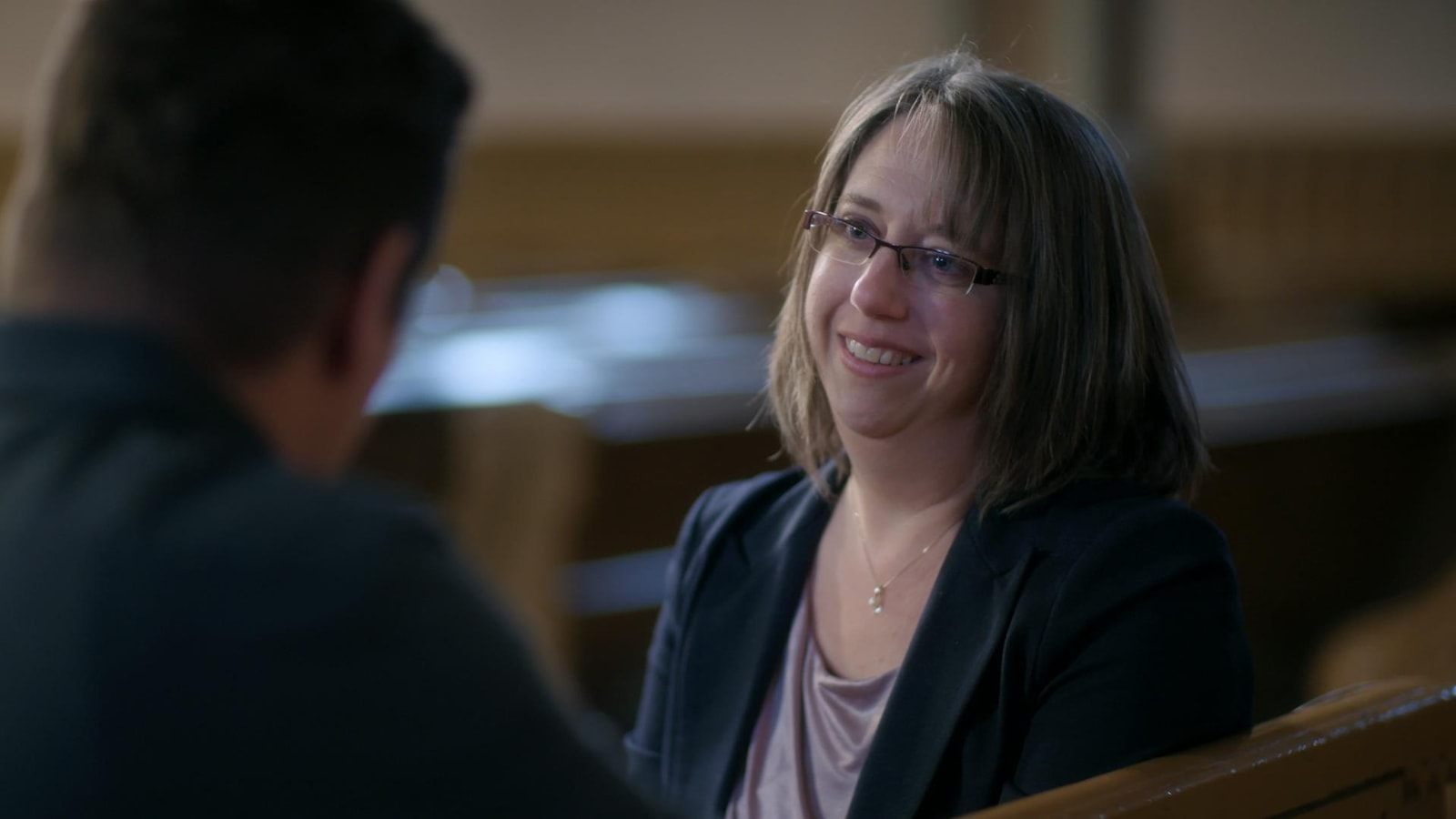 Une femme discute avec Patrick Lagacé sur un banc d'église.