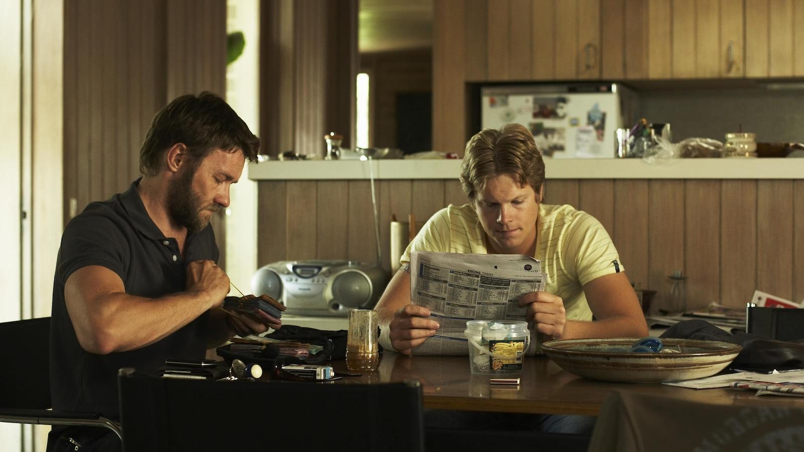 Deux hommes assis à la table de la cuisine côte à côte