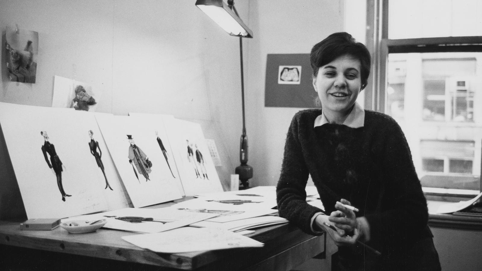 Une femme souriante devant une table de travail où sont installés quelques dessins de costumes.
