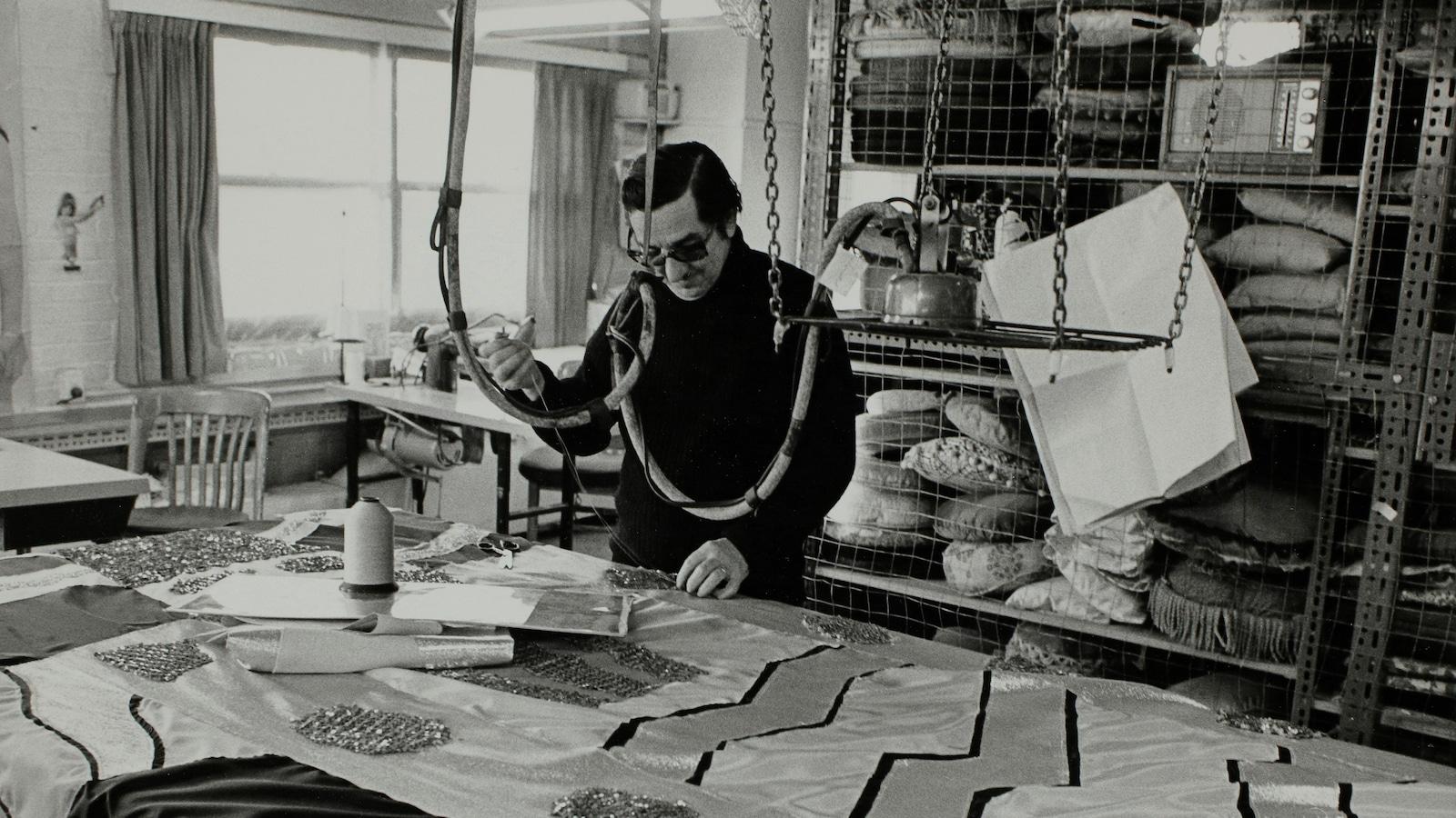 Un homme avec des lunettes est devant une table recouverte de tissus brodés. Derrière lui une étagère contient plusieurs coussins.
