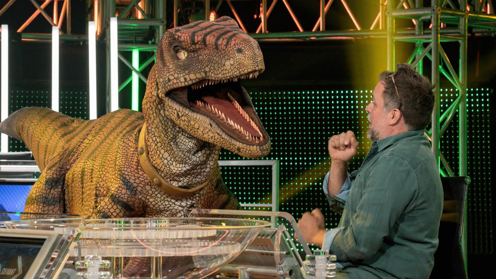 Stéphane Bellavance effrayé devant un dinosaure qui lui parle ou veut le manger.