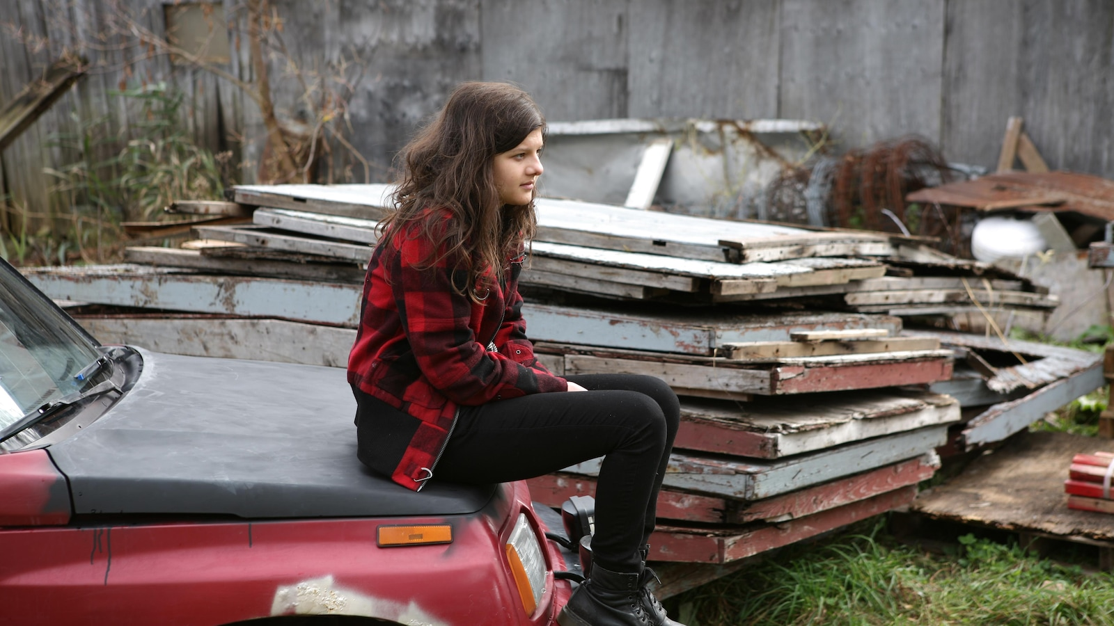 Une jeune fille assise sur le capot d'une voiture, dans une cour à scrap.