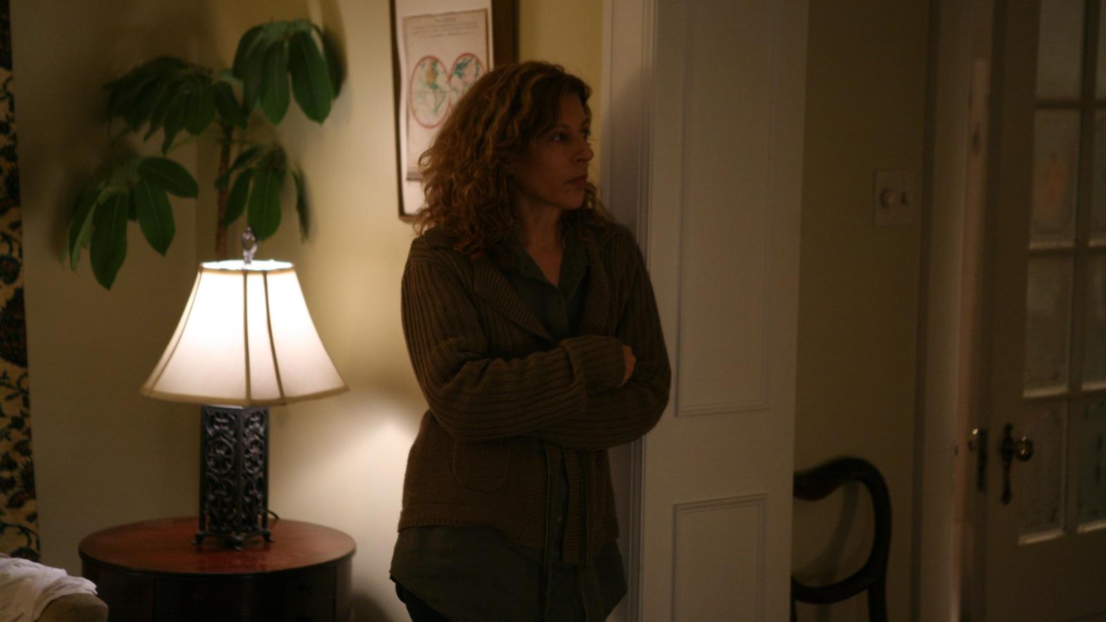 Une femme, dans un appartement, appuyée contre un cadre de porte.