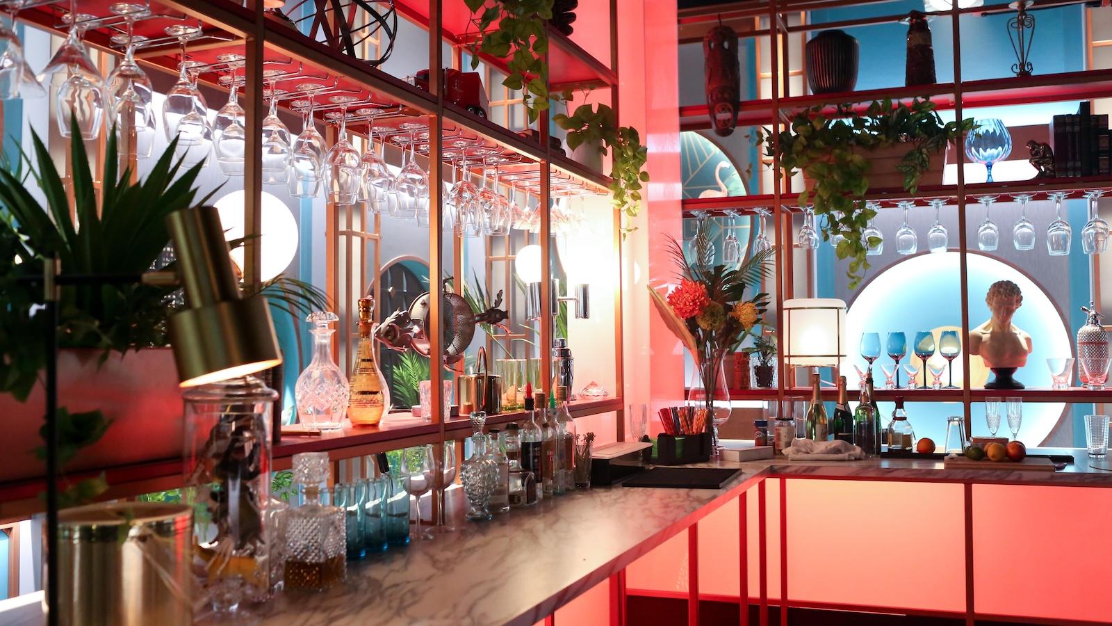 Le bar, avec ses verres et ses bouteilles, est lumineux et coloré.