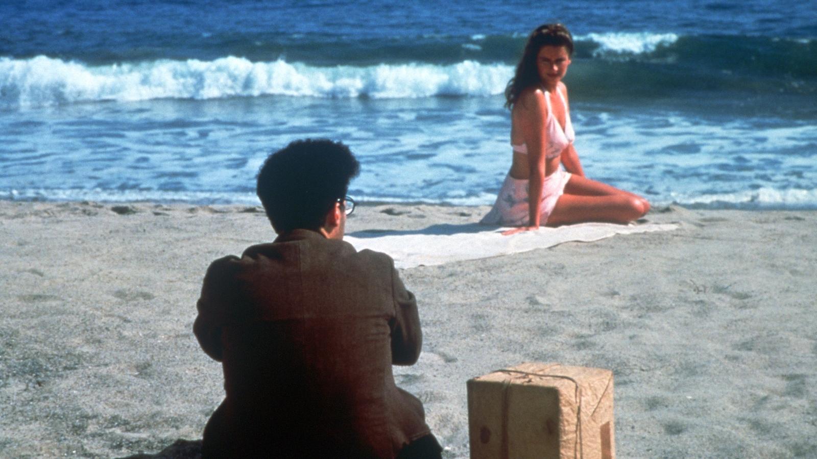 Un homme assis sur la plage, de dos, face à une jeune femme en maillot.