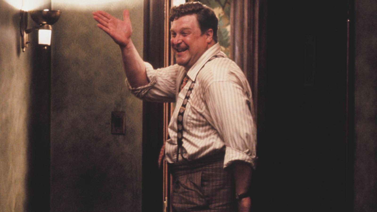 Un homme sort d'une pièce en souriant et en levant la main.