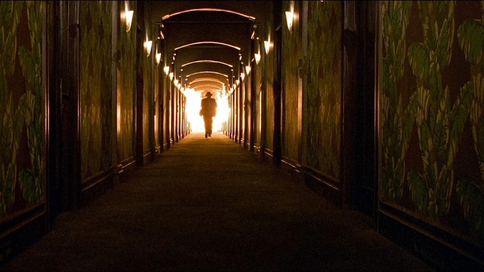 Un homme au fond d'un couloir en feu.