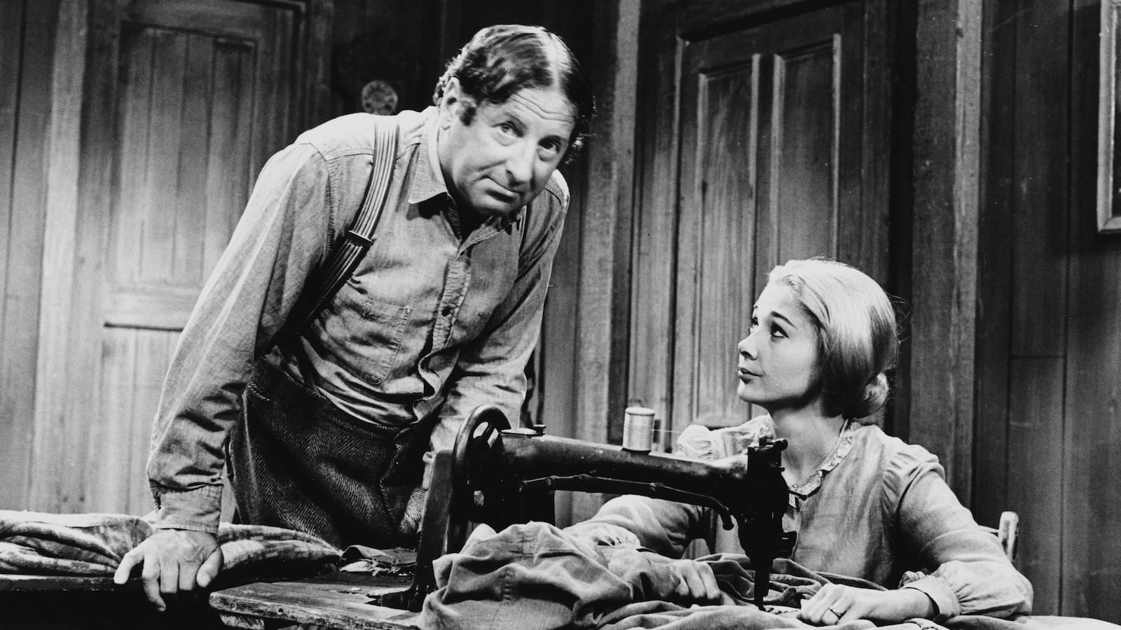 Dans leur maison, Séraphin (Jean-Pierre Masson) se penche vers Donalda (Andrée Champagne) qui est assise derrière un moulin à coudre.