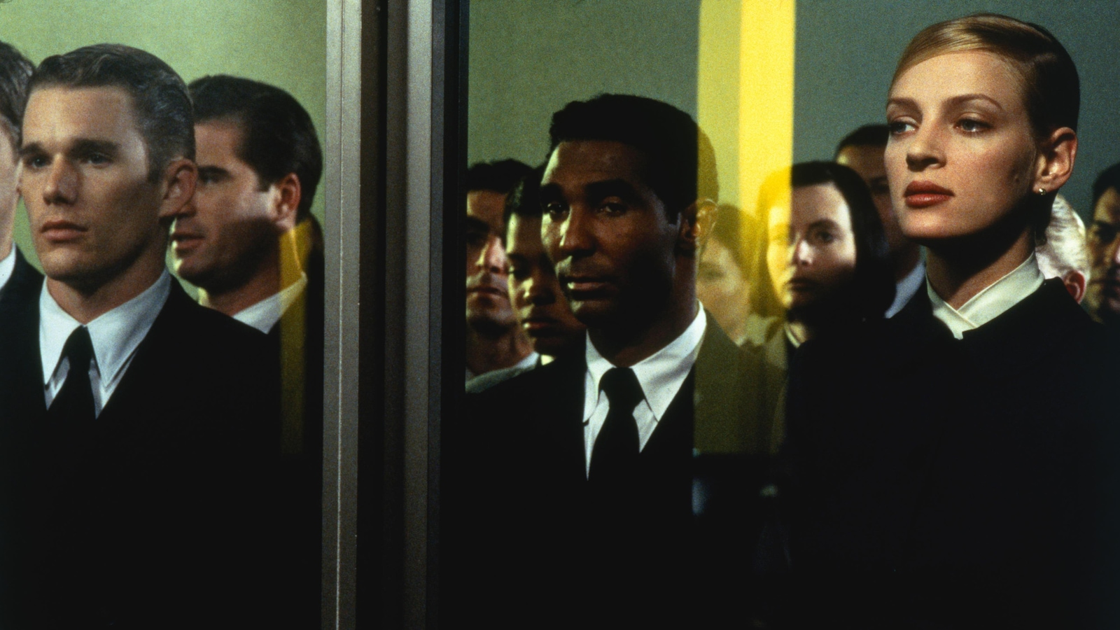 Des femmes et des hommes en costumes noirs, derrière une porte vitrée