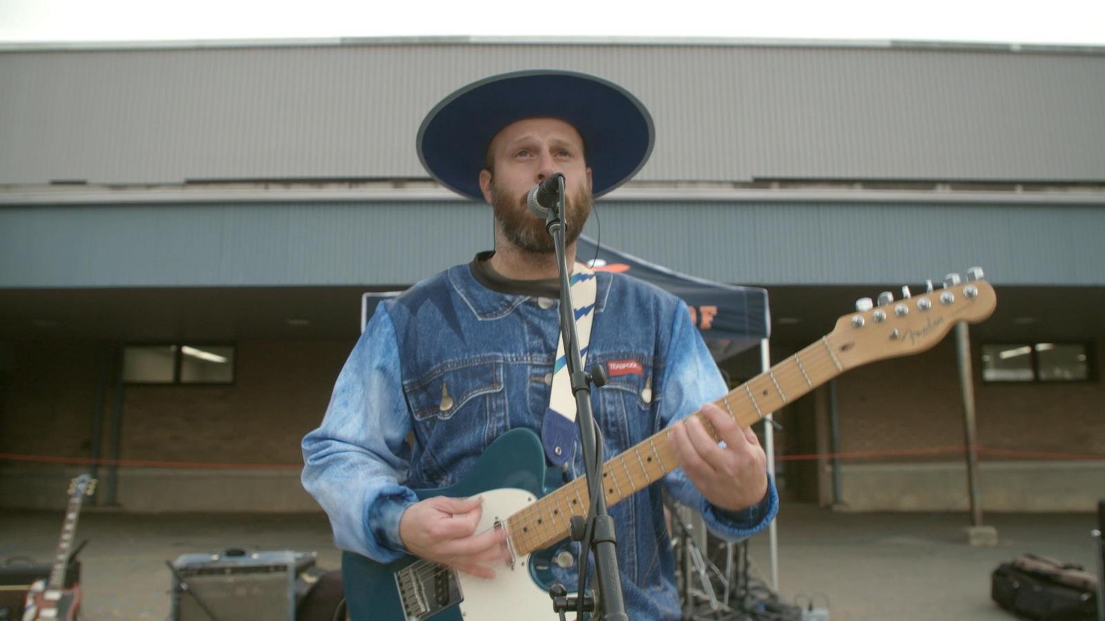 Le chanteur tient sa guitare et chante dehors.
