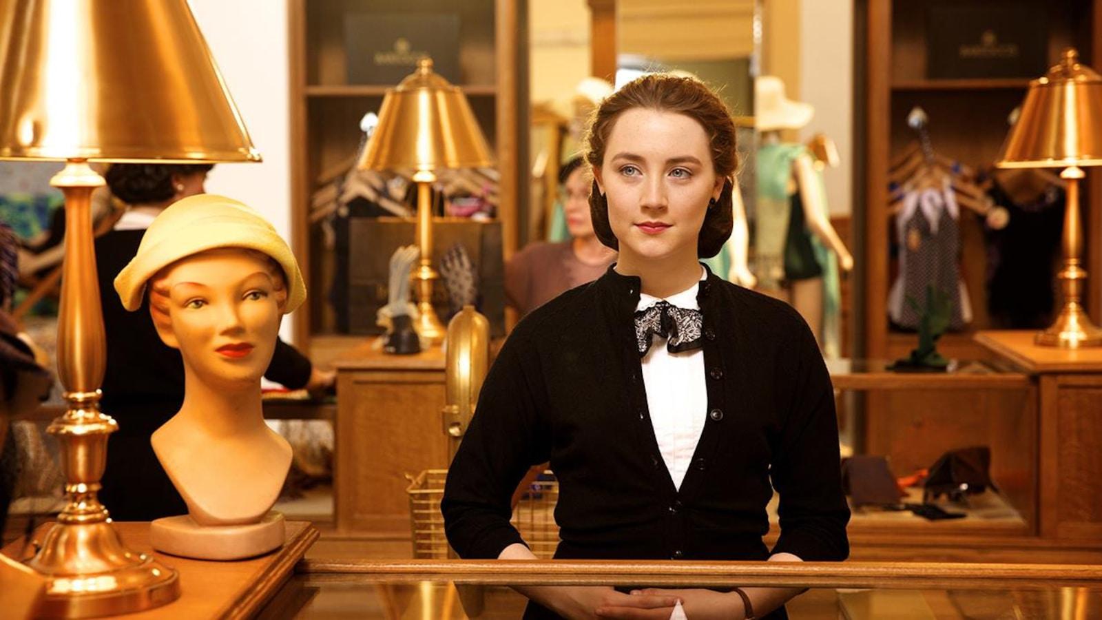 Une jeune femme en tenue sombre, les mains croisées, derrière un comptoir de vente d'un grand magasin