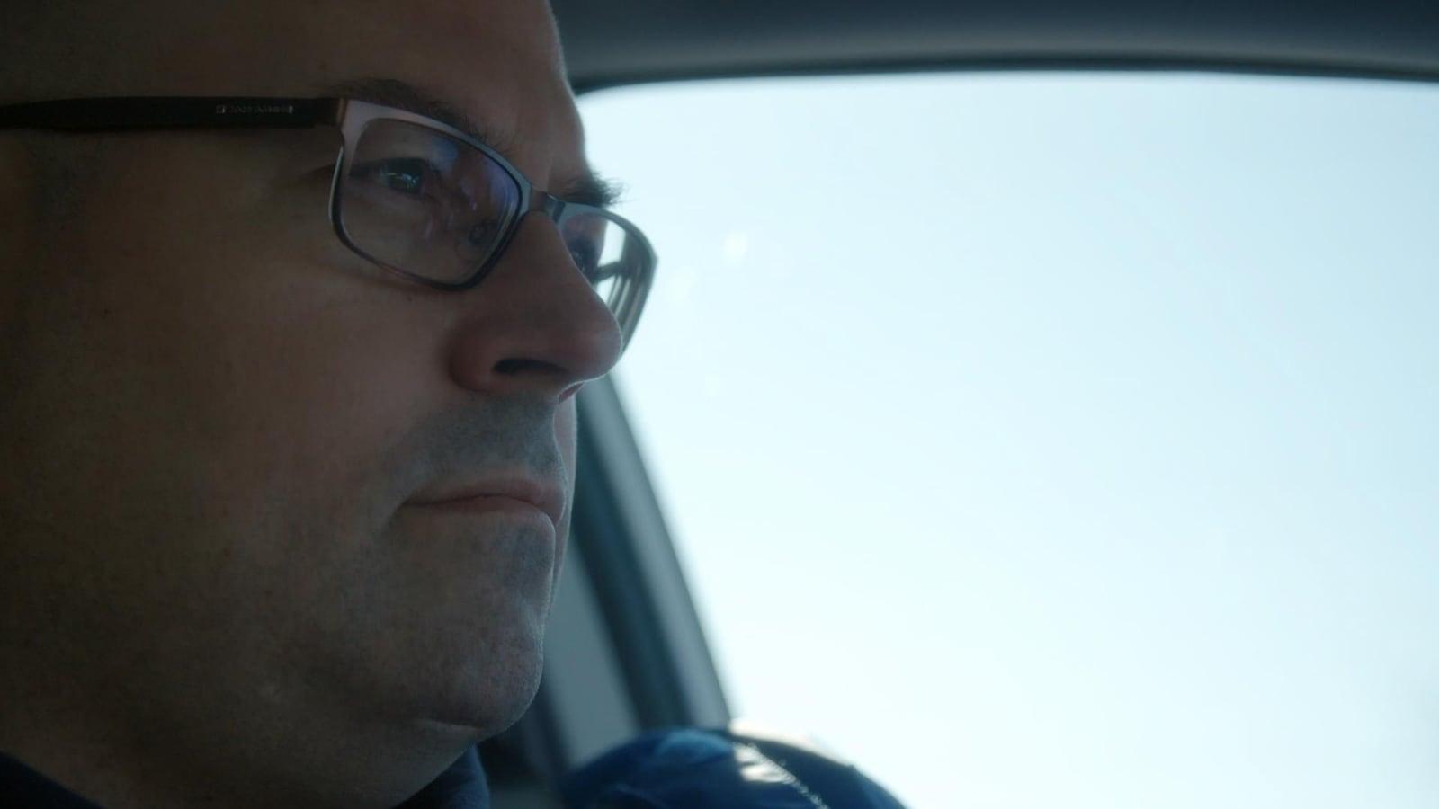 Dans une voiture, le visage d'un homme qui porte des lunettes et qui regarde au loin.