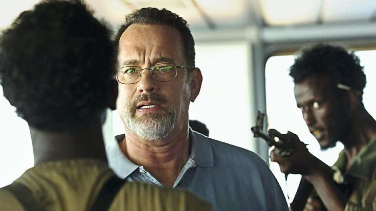 Un homme (Tom Hanks) tenu en joue par deux hommes armés.