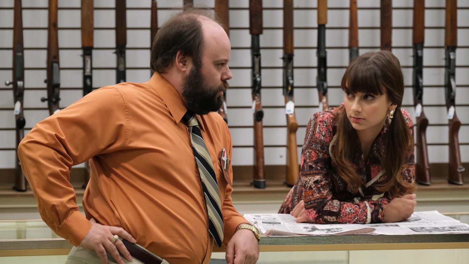 Les deux personnages sont dans un magasin d'armes à feu.