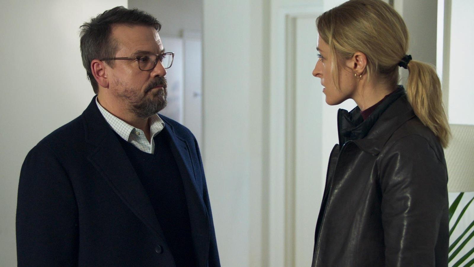Henri Lacombe (Claude Legault) et Simone Vallier (Christine Beaulieu) sont debout face à face et discutent.