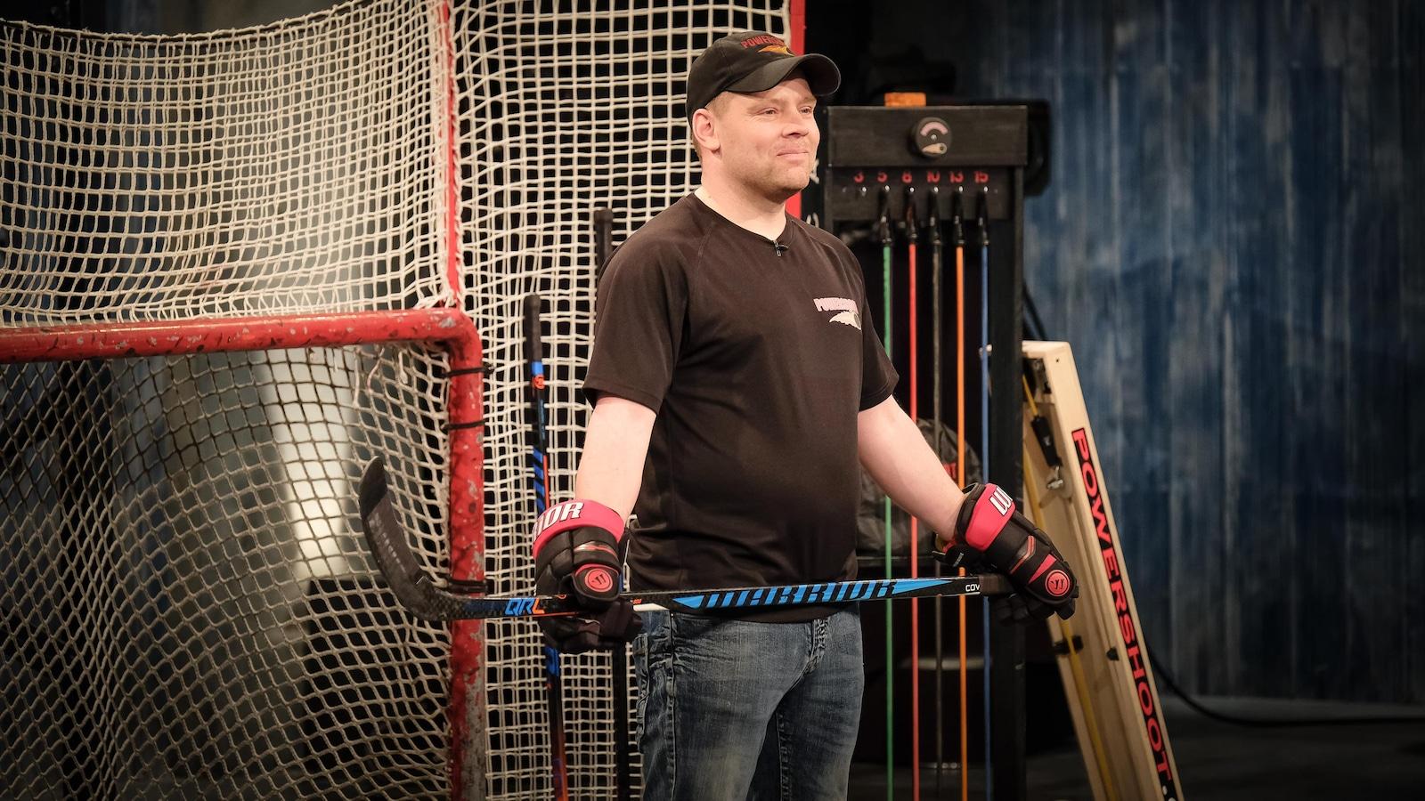 Devant un filet de hockey, un homme tient son bâton à deux mains.