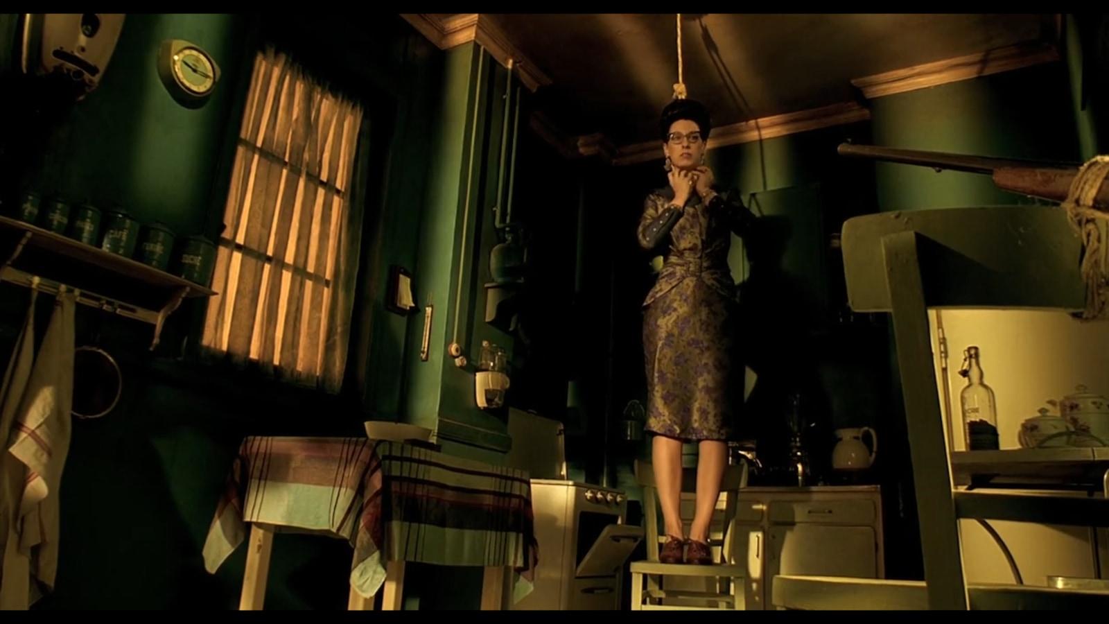 Une femme debout sur une chaise, un noeud coulant autour du cou.