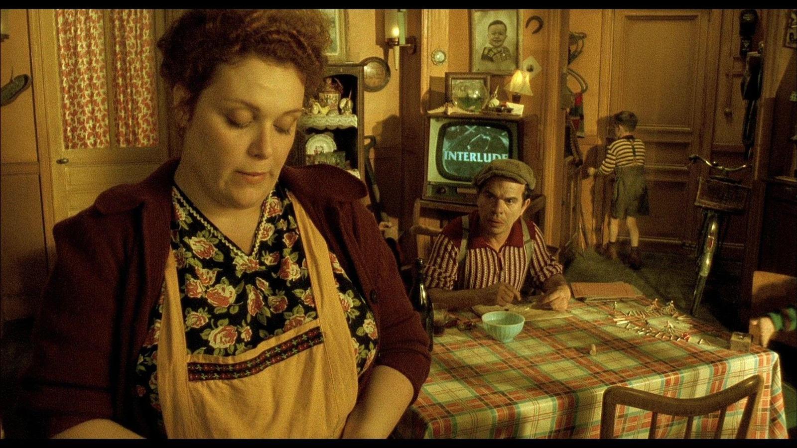 Un homme à table, une femme en tablier en avant-plan.