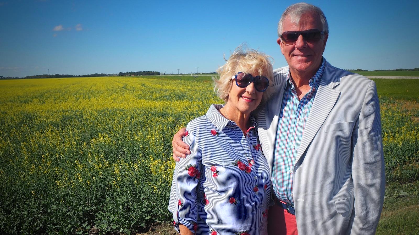 Le couple pose devant un champ.
