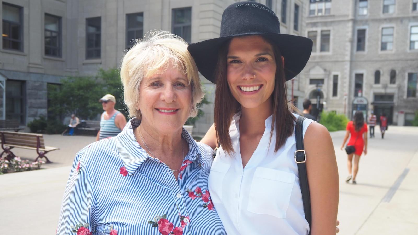 Denise Bombardier porte une robe à fines rayures bleues et blanches et à imprimés de fleurs. Une femme est à ses côtés. Elle porte un chapeau noir et une chemise blanche sans manches.