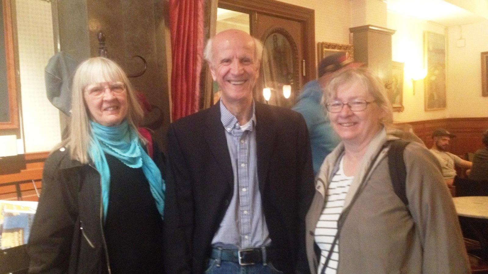 Un homme entouré de deux femmes dans une salle de réception.