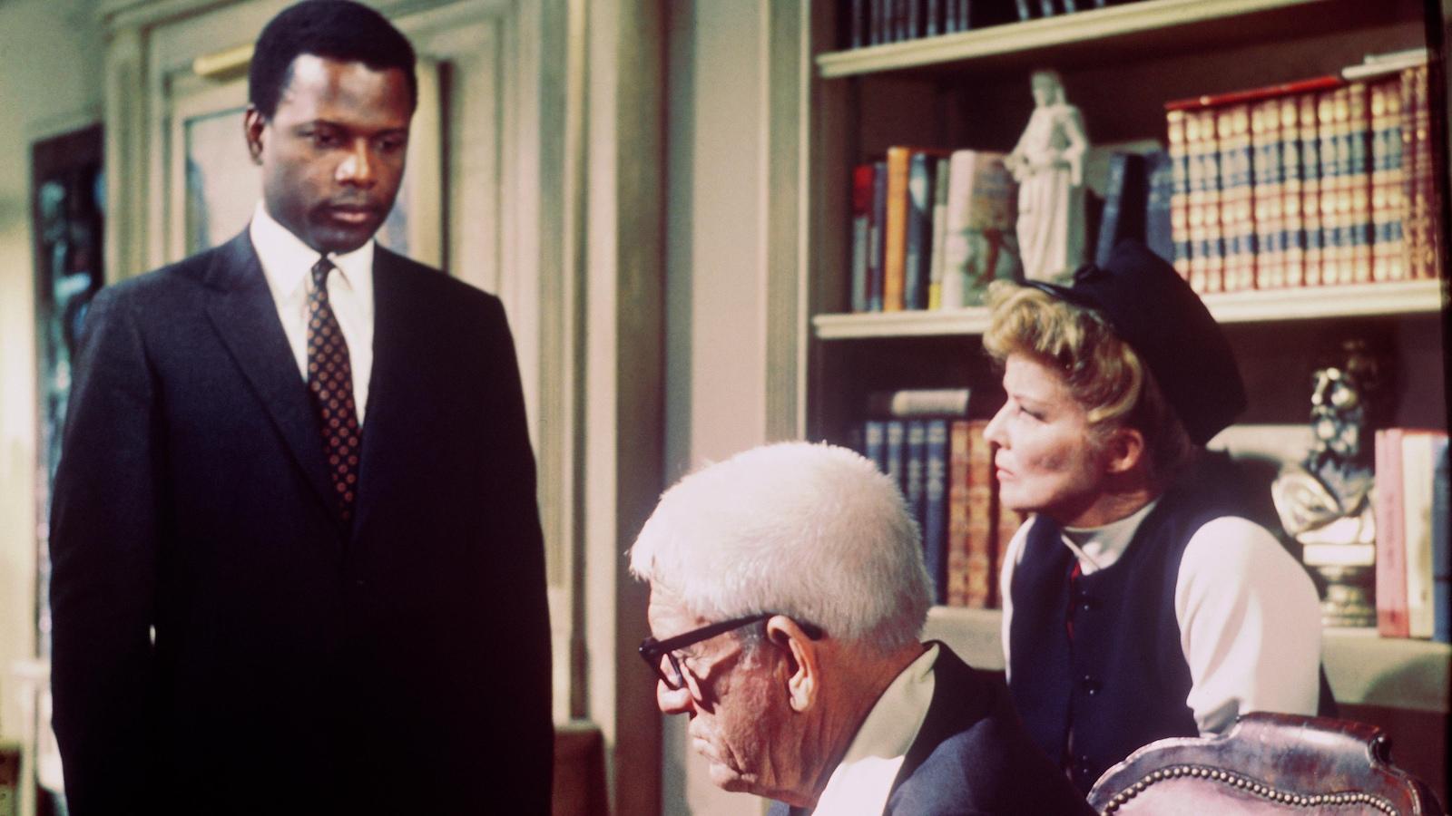 Un jeune homme noir debout, devant un couple de personnes plus âgées et blanches.