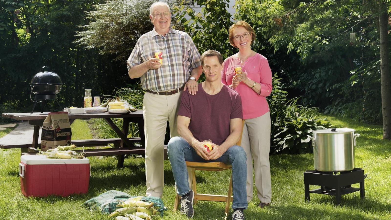 Lors d'une épluchette de blé d'Inde, François Morency est assis sur une chaise, ses parents sont derrière lui.