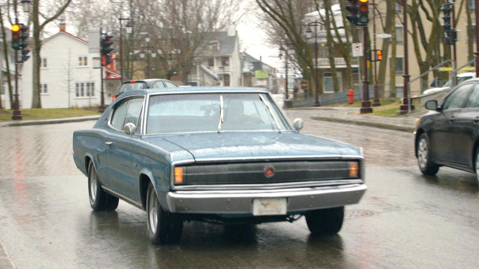 Une voiture de collection roule dans la rue sur une chaussée mouillée.