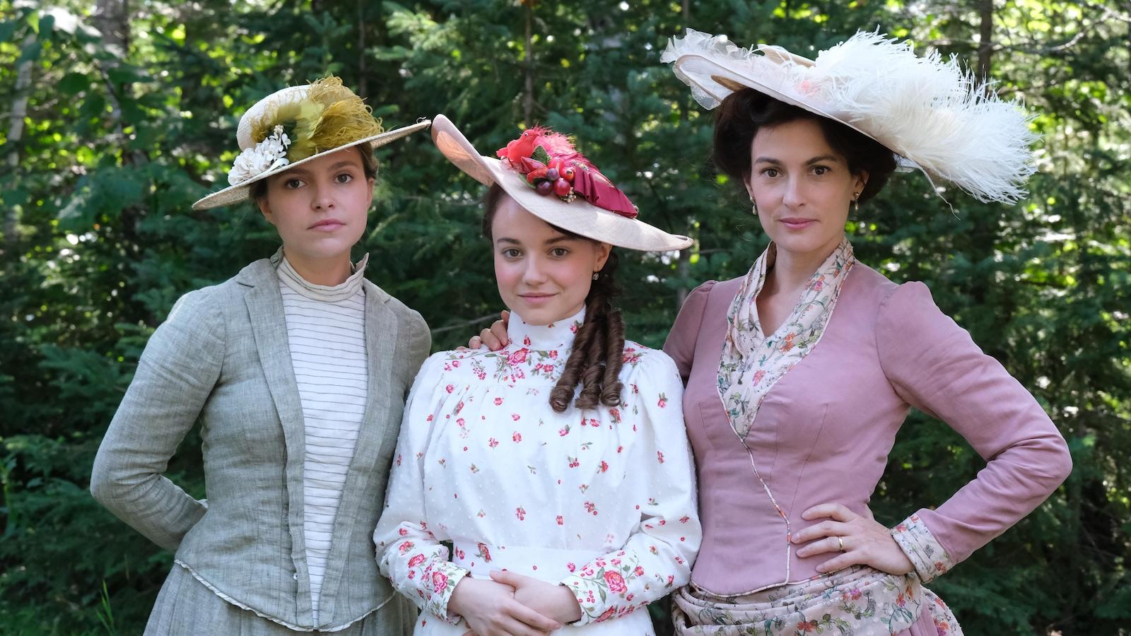 Sarah-Jeanne Labrosse, Romane Denis et Madeleine Péloquin en robes d'époque élégantes pour un mariage dans Les pays d'en haut.