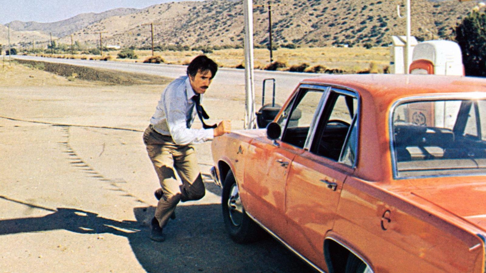 Un homme court à côté d'une voiture rouge garée dans une station essence