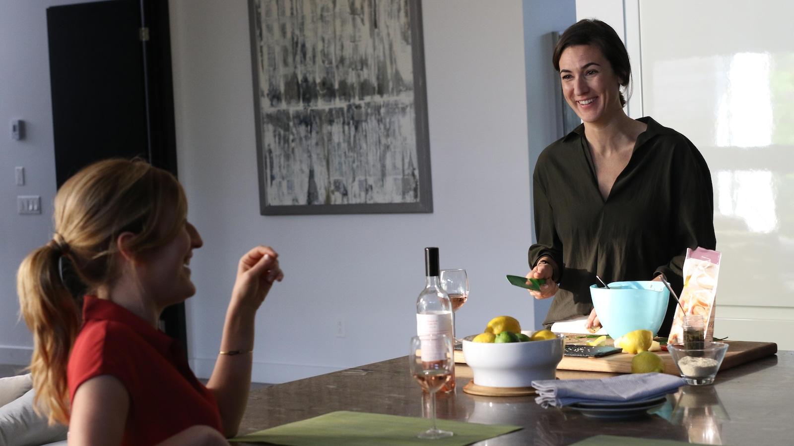Deux comédiennes échangent un rire complice dans une cuisine.