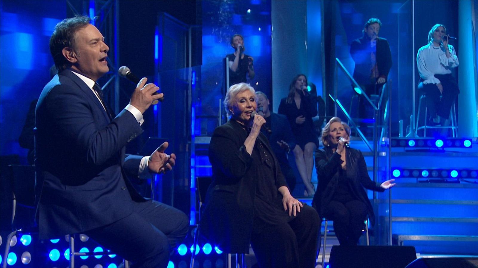 Mario Pelchat, Patsy Gallant et France Castel, chantent sur un tabouret, micro à la main.