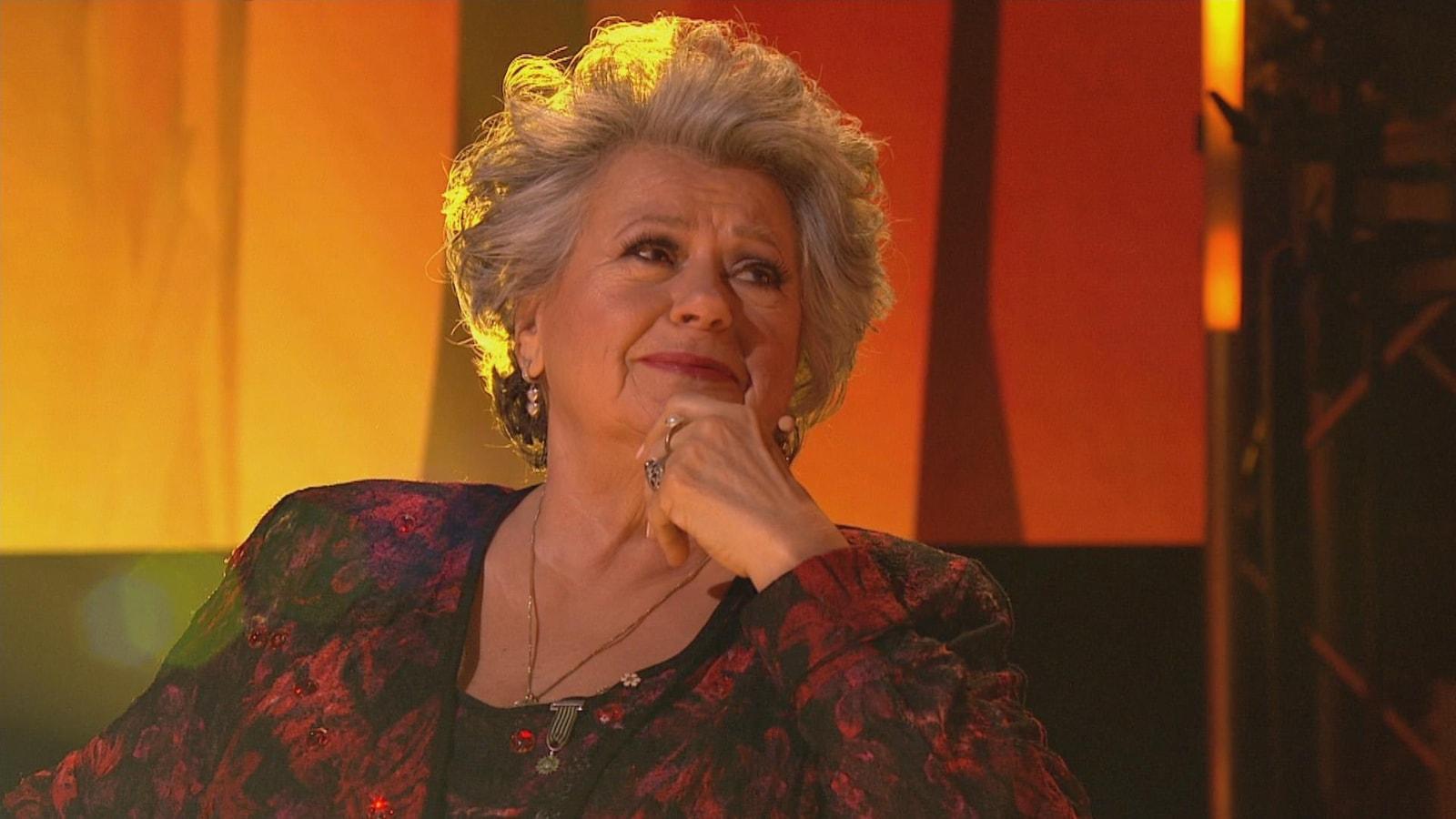 Ginette Reno regarde une prestation, attendrie.