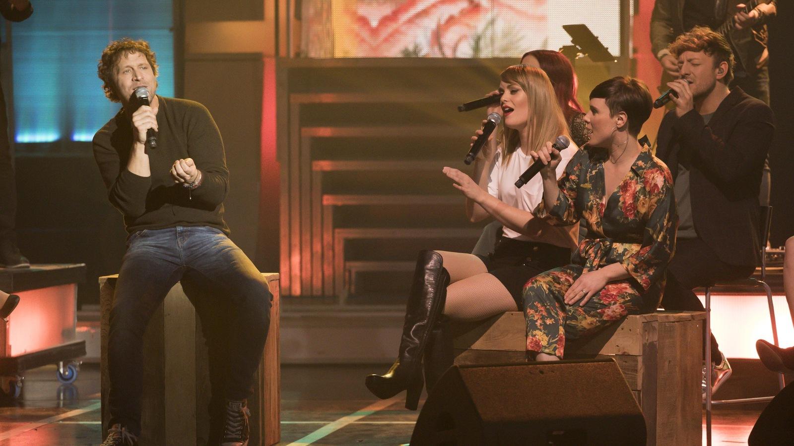 Kevin Parent est assis sur une caisse et chante avec son micro. Pascale Picard et Andréanne A. Mallette sont les choristes.