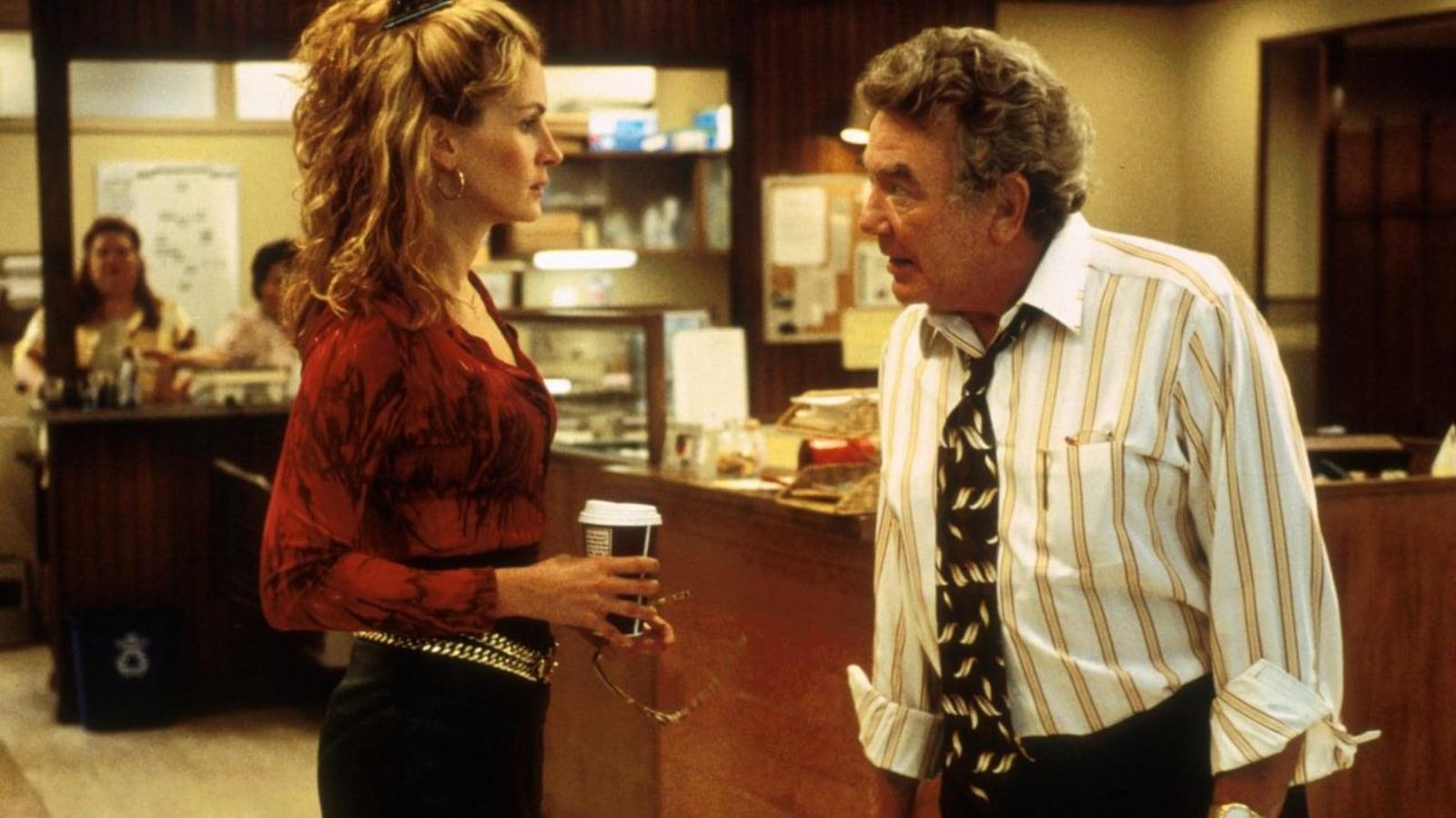 Une femme, un café à la main, discute avec un homme en chemise et cravate dans un bureau