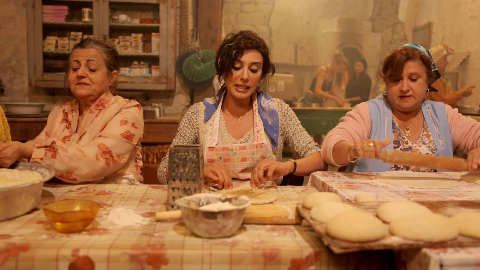 Des femmes assises en train de faire la cuisine.