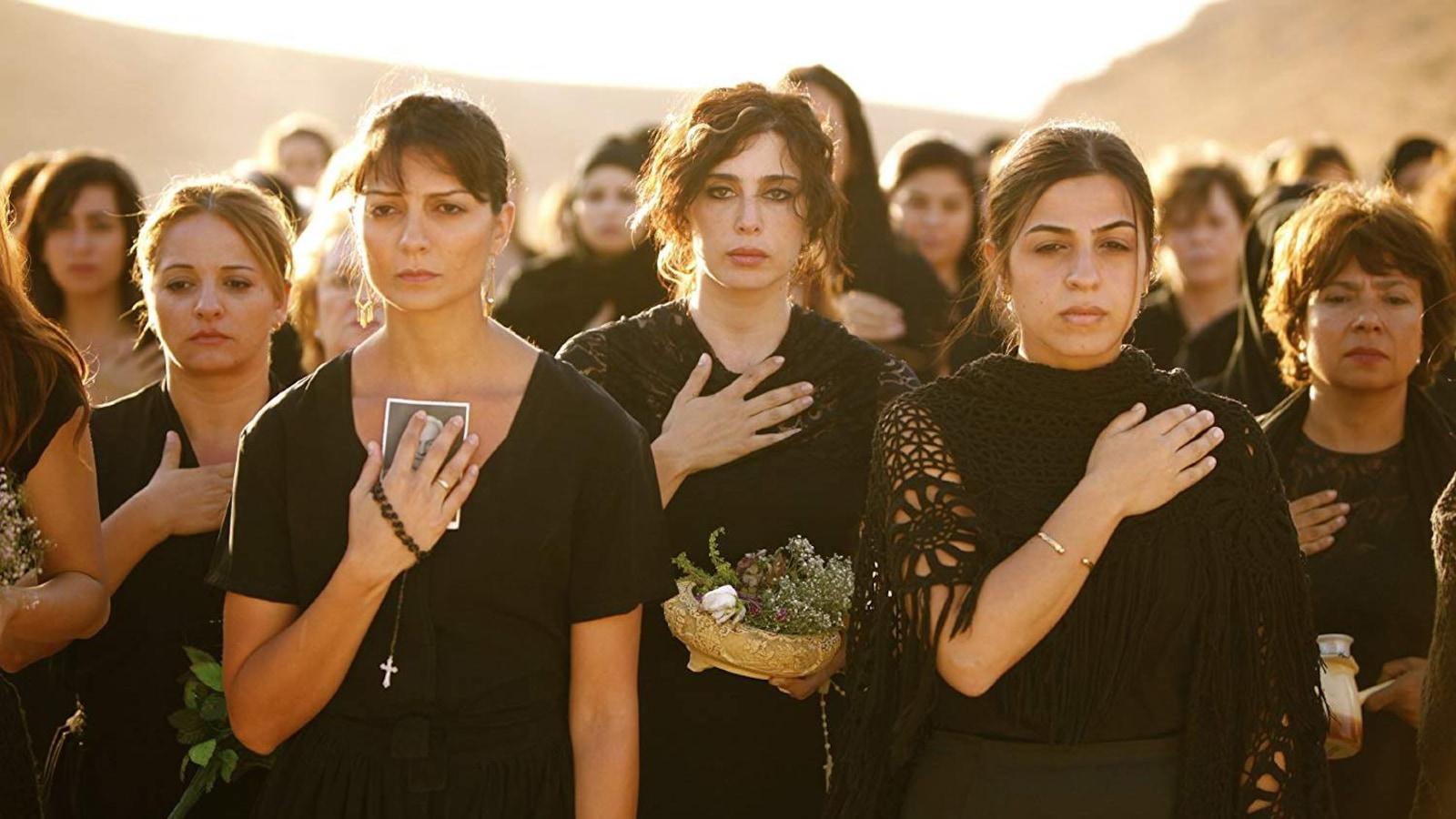 Un groupe de femmes habillées en noir, la main sur le coeur.
