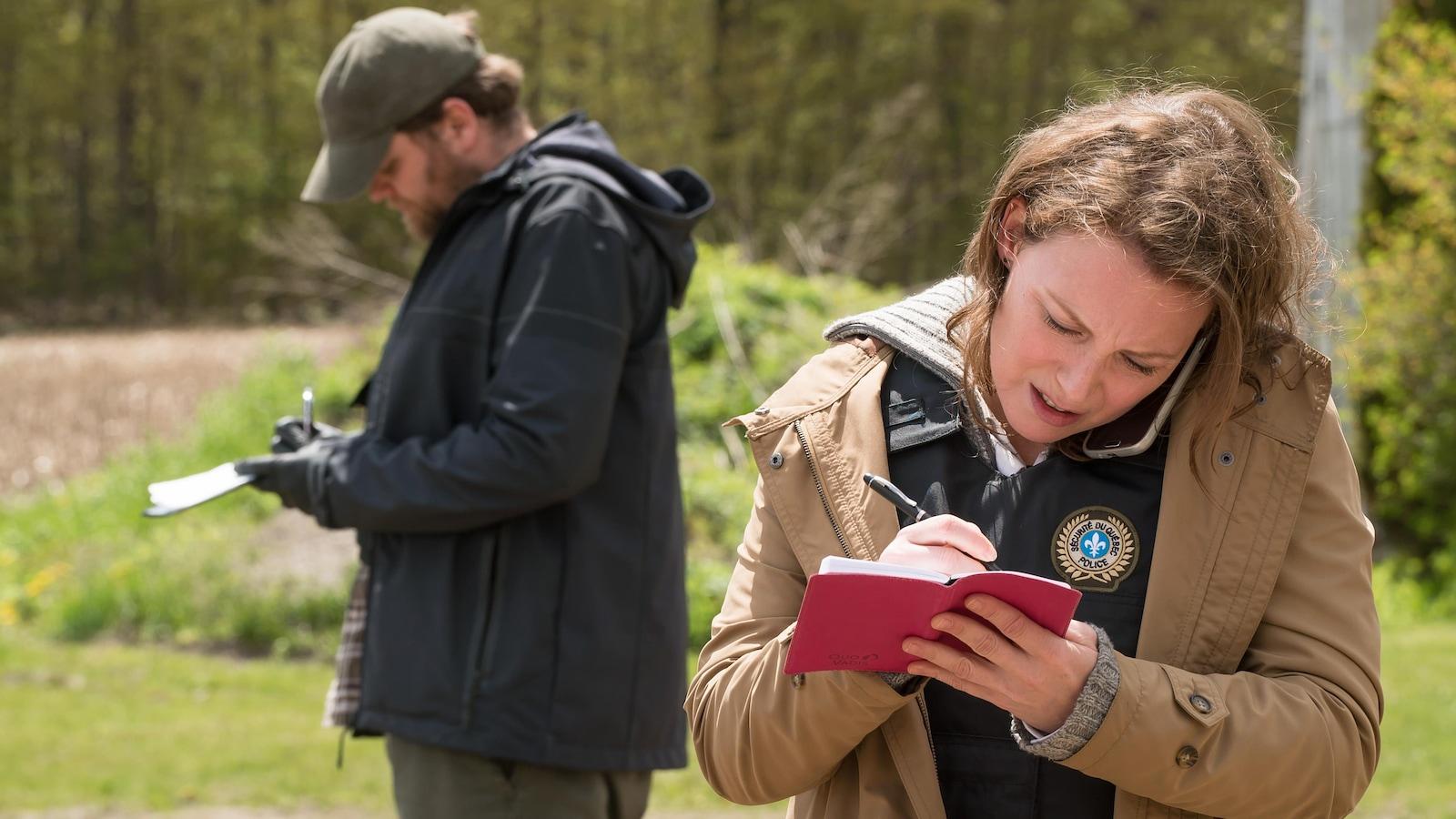 L'oreille collée au cellulaire, l'enquêtrice prend des notes dans un carnet.
