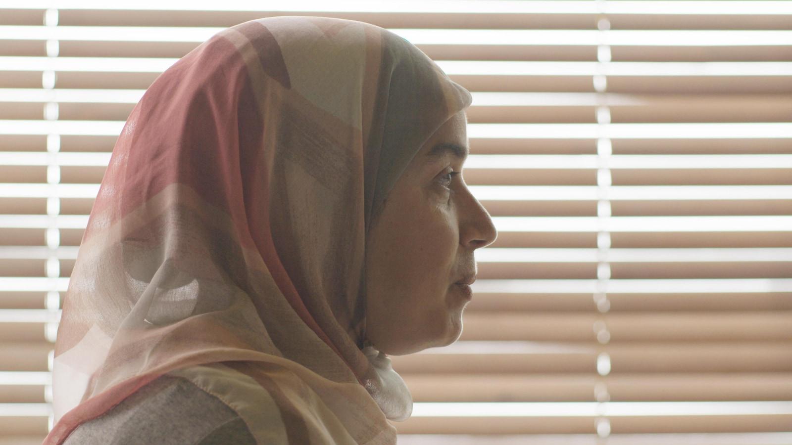 Une femme portant un hijab de profil devant des stores.