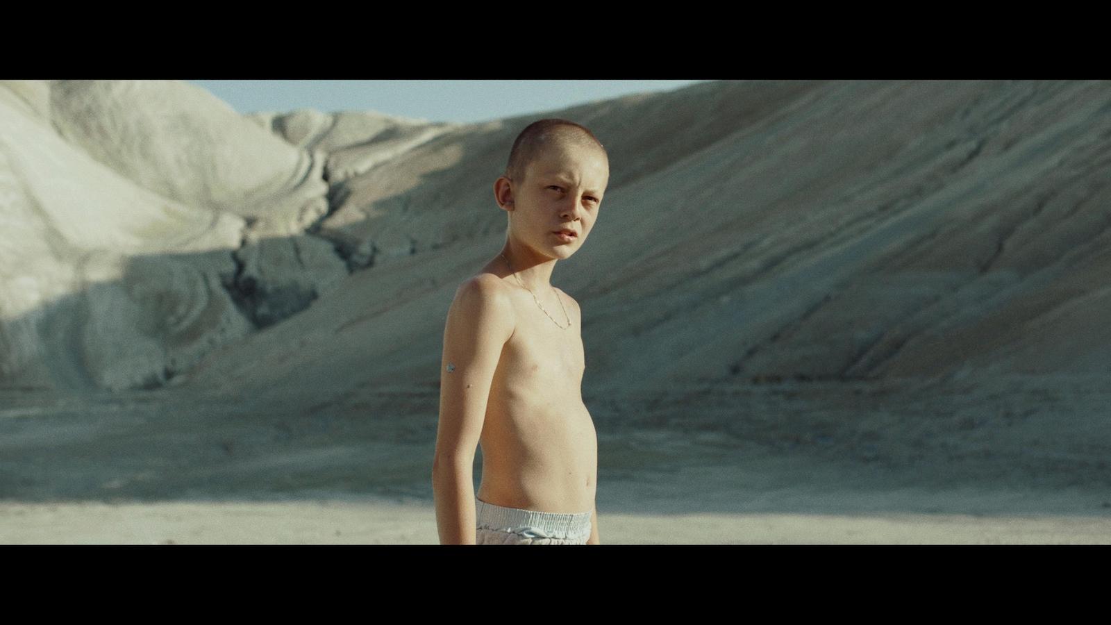 Un jeune garçon torse nu et crane rasé, dans un désert