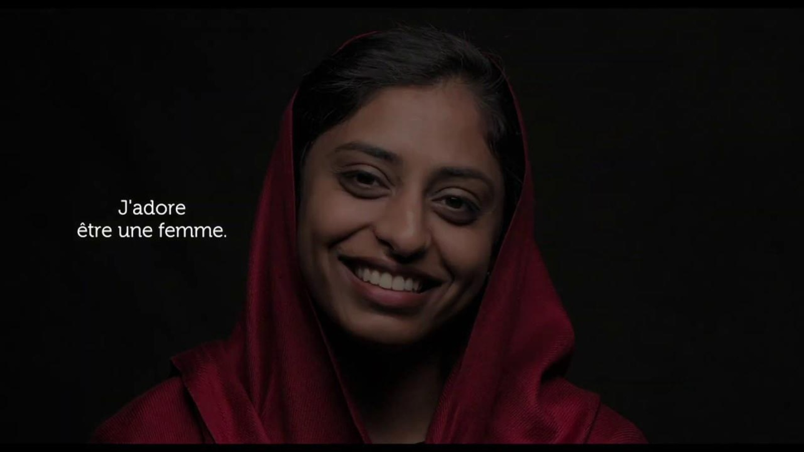 Une femme souriante, en gros plan sur fond noir et sur sa droite, les mots J'adore être une femme.