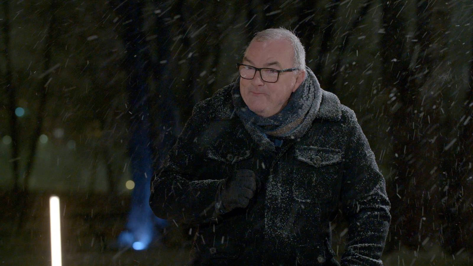 Il est dehors le soir sous la neige qui tombe.