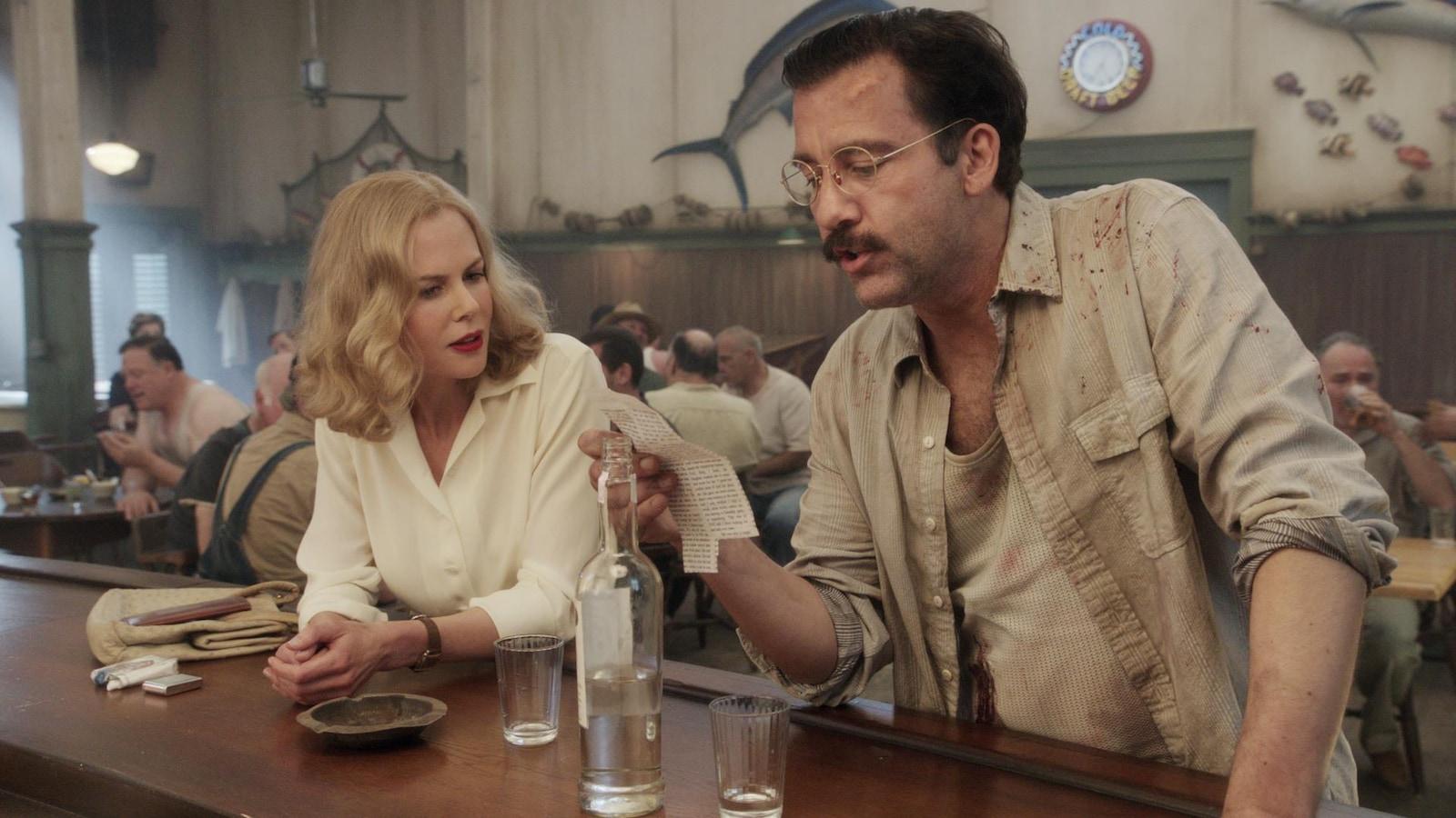Une femme et un homme attablés à un comptoir de bar.