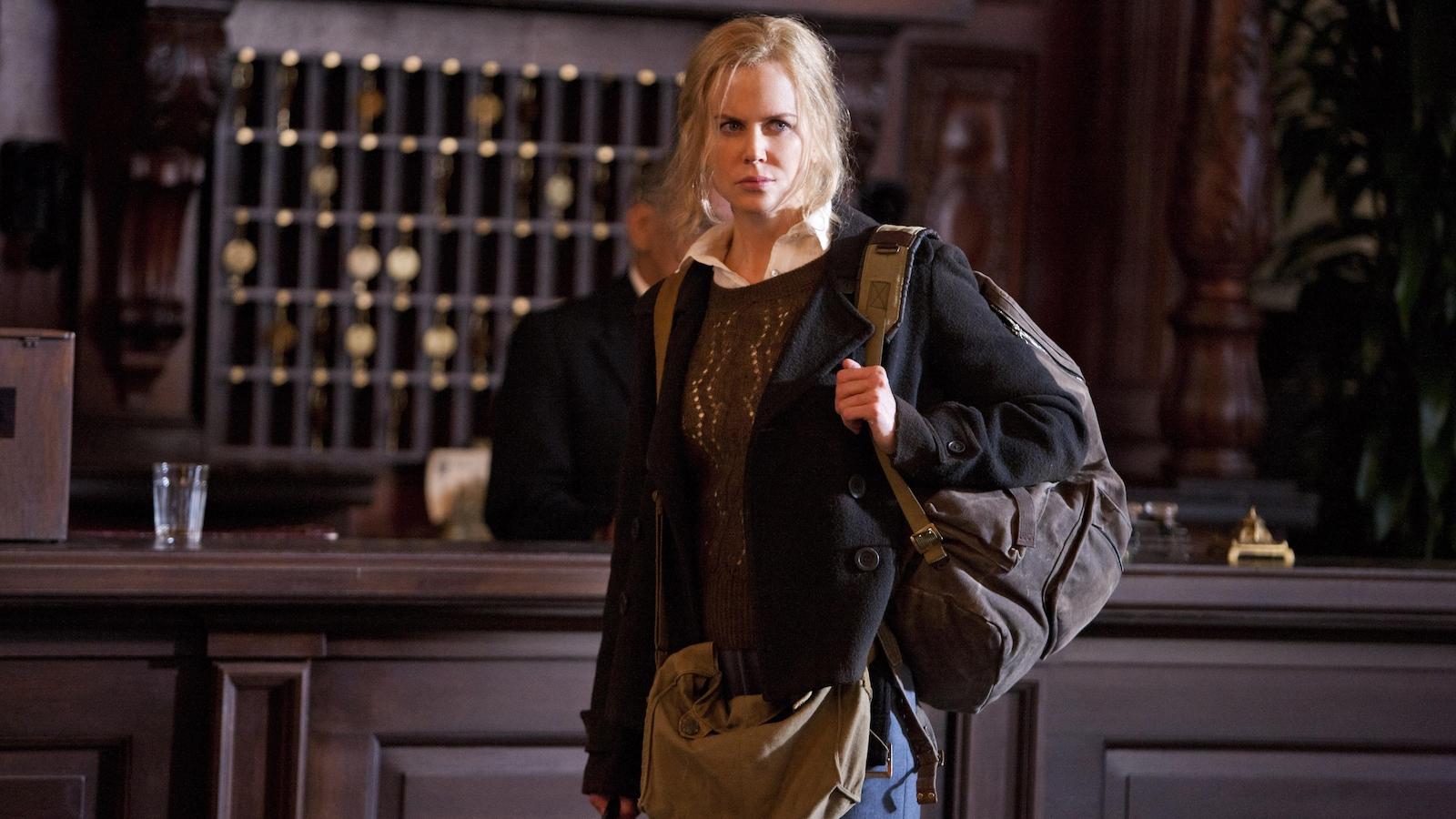 Une femme dans le hall d'un hôtel, une valise à la main