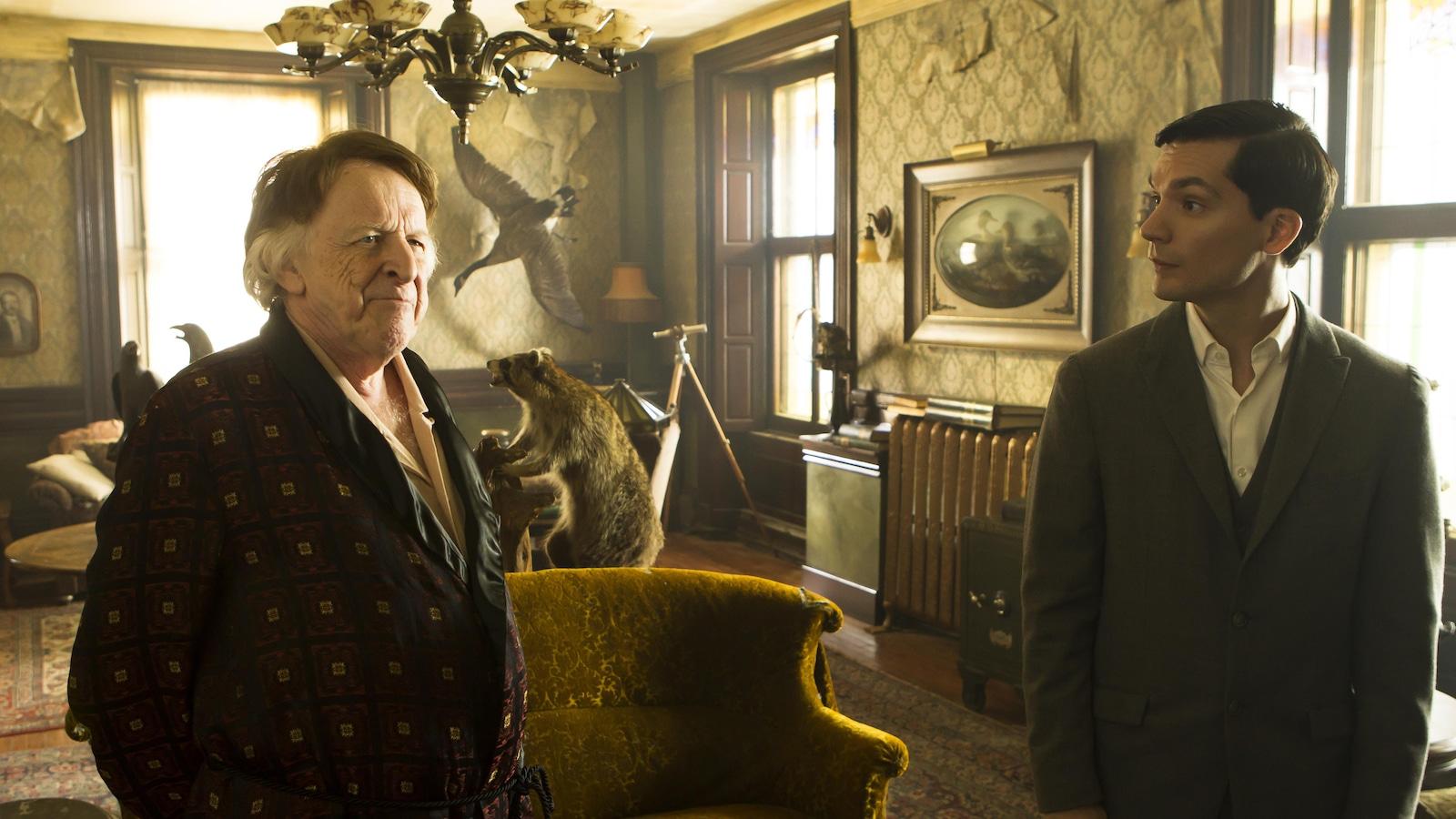 Deux hommes, dont un en robe de chambre, dans un salon richement décoré.