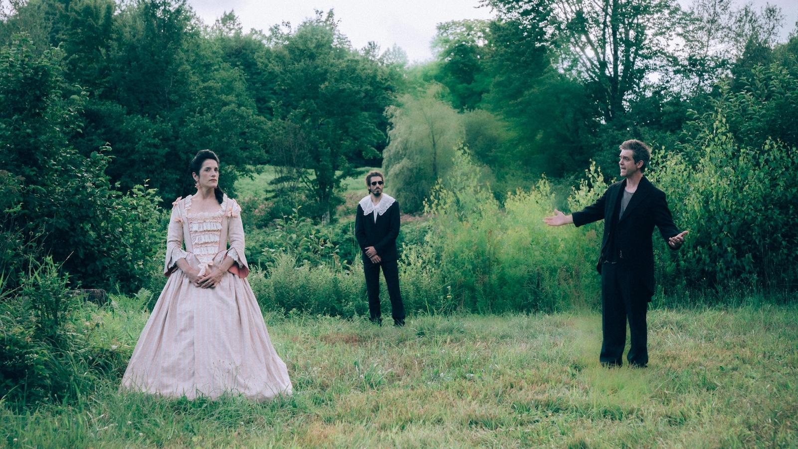 Dans un champ, deux hommes et une femme (Eve Duranceau) dans une robe d'époque.