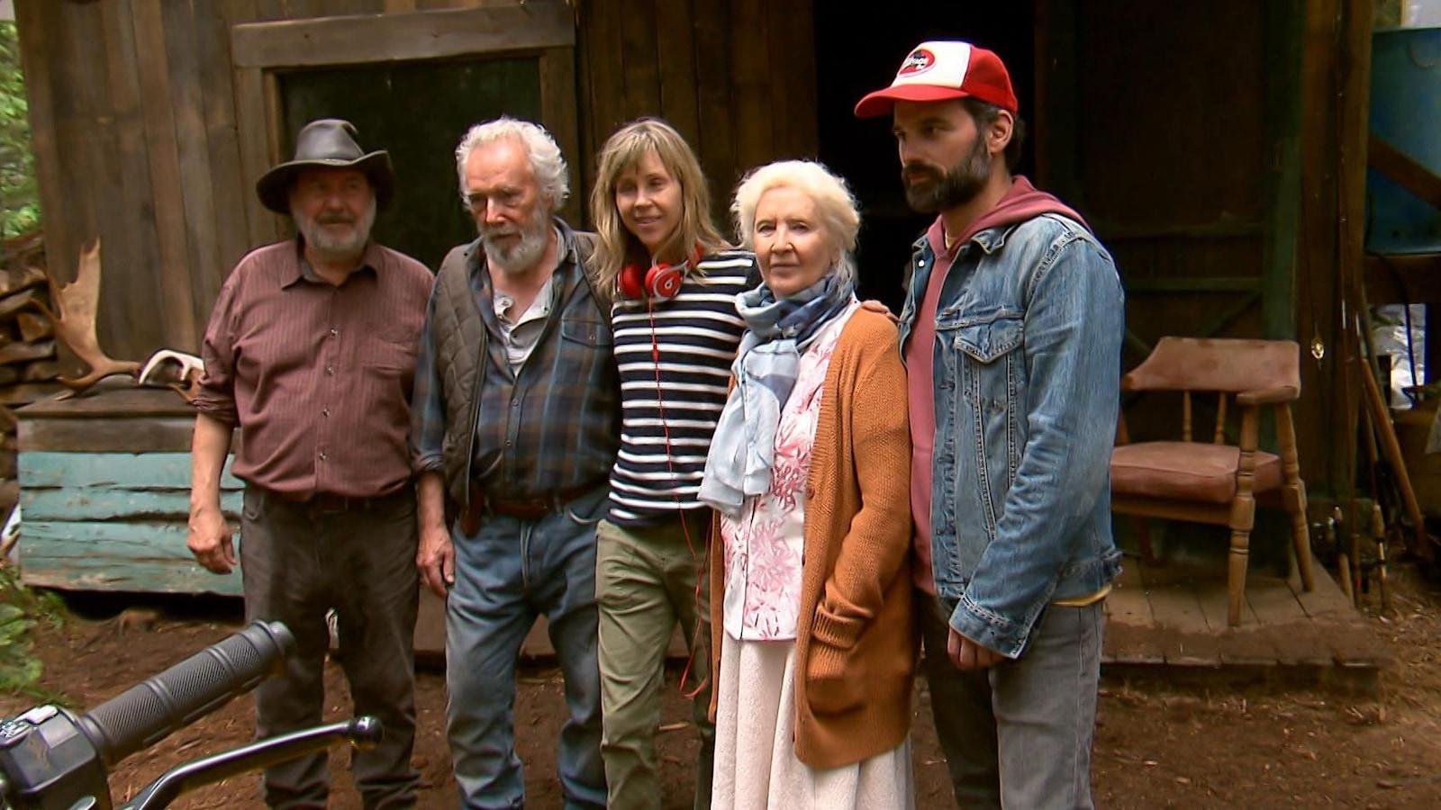 5 personnes sont côte à côte devant une cabane délabrée dans la forêt.