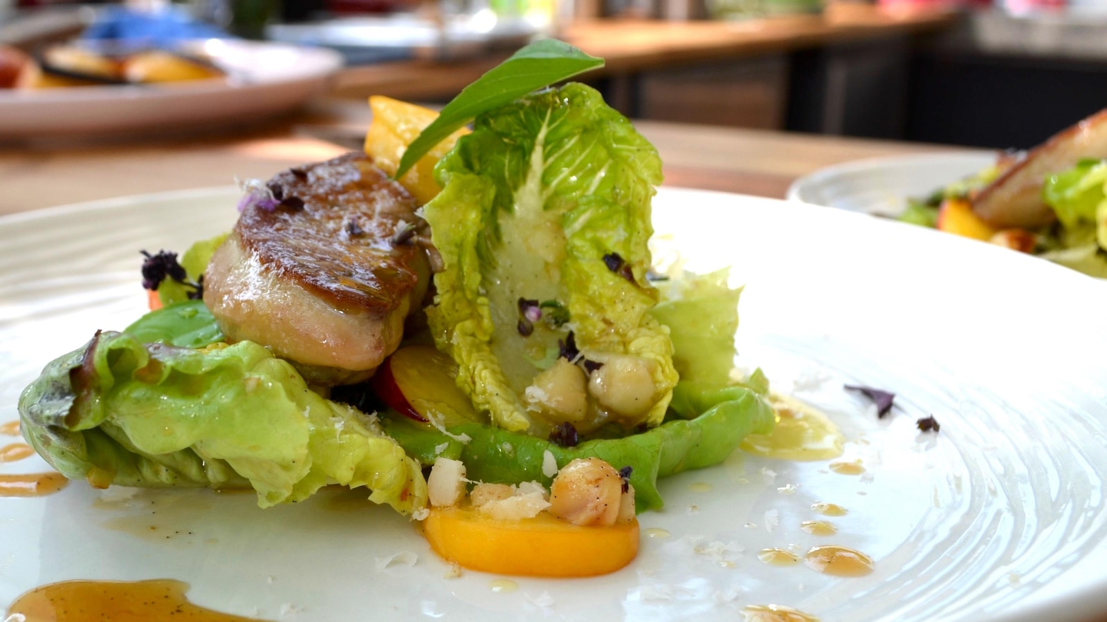 Une assiette composée de laitue, de pêches et de foie gras.