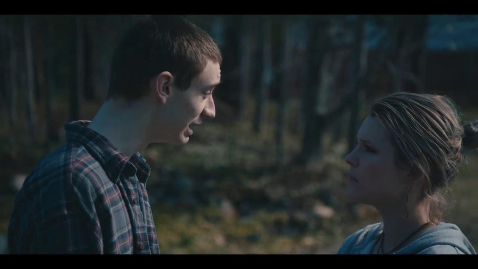 Un jeune homme et une jeune femme face à face, à l'extérieur.