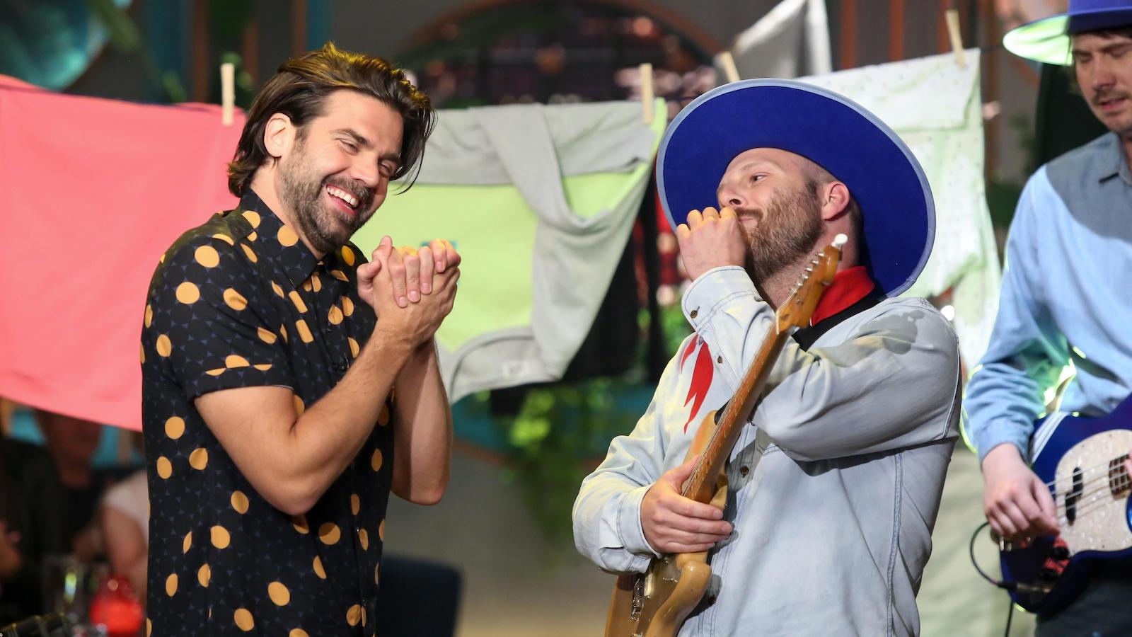 Les deux hommes rient.